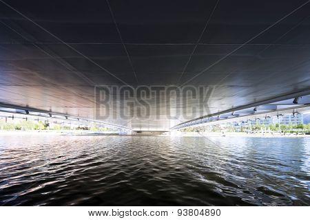 flowing river below bridge of modern city
