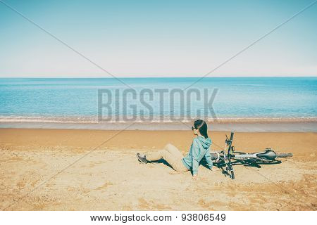 Woman Resting With Bicycle On Beach