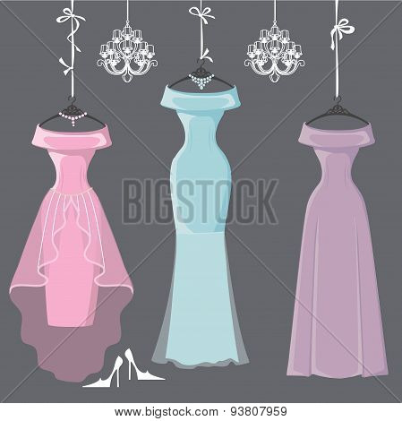 Three long bridesmaid dresses hang on ribbons
