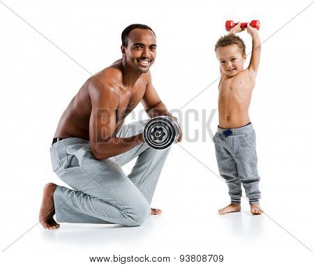 Cheerful Father And Son Exercising With Dumbbells And Smiling