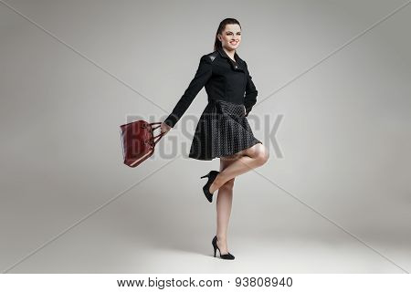 Elegant glamour woman wearing black skirt and blouse a grey background