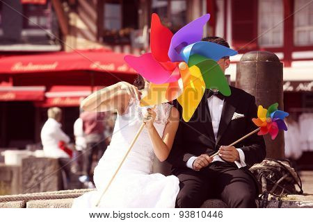 Bride And Groom Playing With Windmill Propeller
