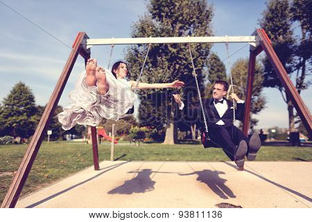 Bride And Groom Playing On A Swing Set