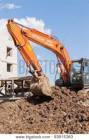 Orange Hitachi Digger Moving Soil