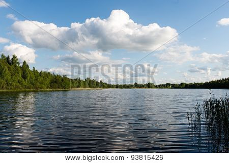 White Clouds On The Blue Sky Over Blue Lake