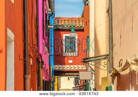 Colorful apartment buildings at very narrow street in Burano, Venice, Italy.