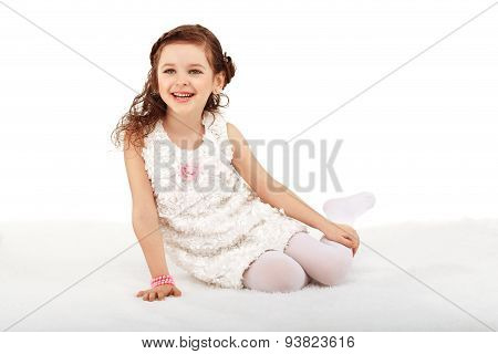 Portrait Of A Pretty Little Fun Fashion Girl Sitting On A Fluffy Rug On The Floor And Having Fun