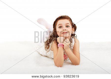 Portrait Of A Pretty Little Fun Fashion Girl Lying On A Fluffy Rug On The Floor