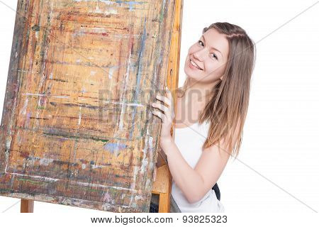 Young smiling woman  hiding behind  easel