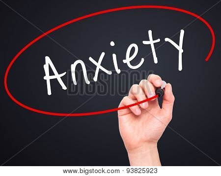 Man Hand writing Anxiety with black marker on visual screen.