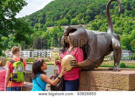 HEIDELBERG, GERMANY - MAY 28, 2015: Tourists photographed a monkey sculpture on the old bridge. Monkey symbolizes the vanity and shamelessness.