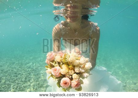 Hands Of A Bride Holding Wedding Bouquet Underwater