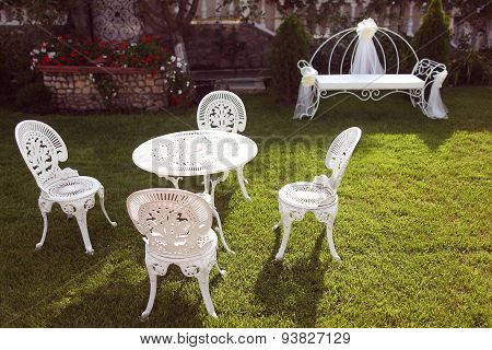 White Cast Iron Chairs And Table In The Garden