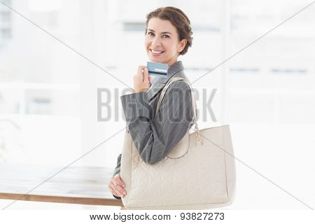 Smiling businesswoman looking at camera and holding credit card in an office