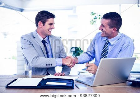 Businessmen shaking hands at desk in the office