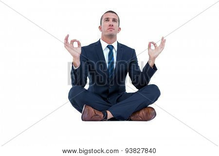 Zen businessman in yoga pose on white background