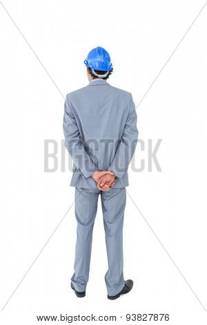 Businessman with helmet turning his back to camera on white background