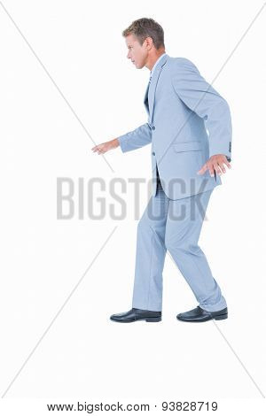 Unsmiling businessman in suit walking on white background