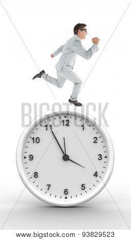Geeky happy businessman running mid air against clock