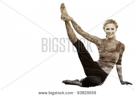 Athletic blonde sitting on floor stretching leg up smiling at camera against rapids flowing along lush forest
