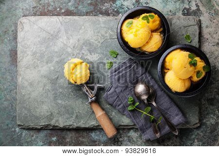 Mango Ice Cream Sorbet With Mint Leaves And Spoon For Ice Cream On Stone Slate Background