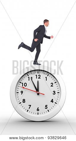 Businessman running against countdown to midnight on clock