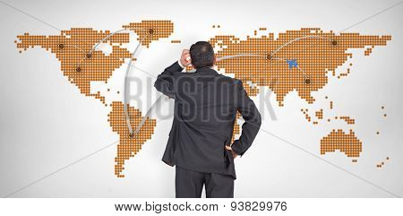 Mature businessman looking and considering against world map with lines