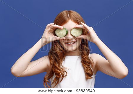 Smiling little girl holding slices of cucumber