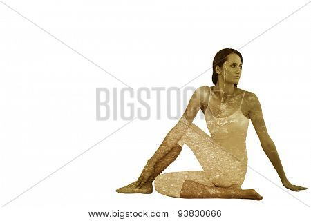 Fit woman doing the half spinal twist pose in fitness studio against forest trail