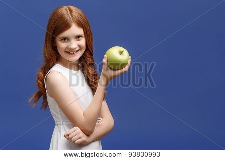 Nice little girl holding apple in one hand