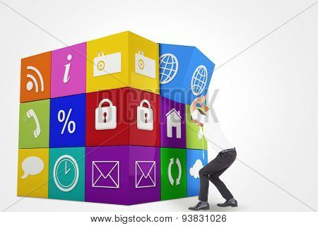 Businessman bending and pushing against app cube