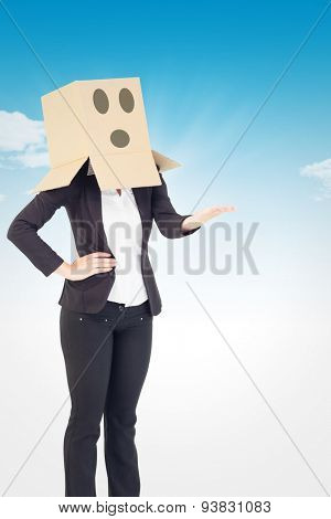Businesswoman showing thumbs up with box over head against blue sky
