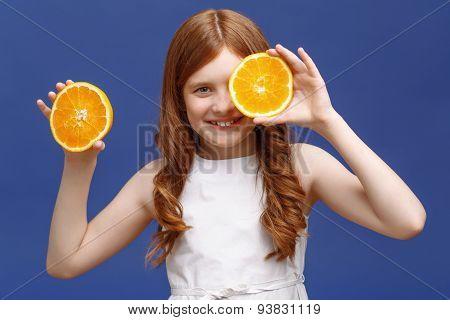 Smiling girl holding halves of orange