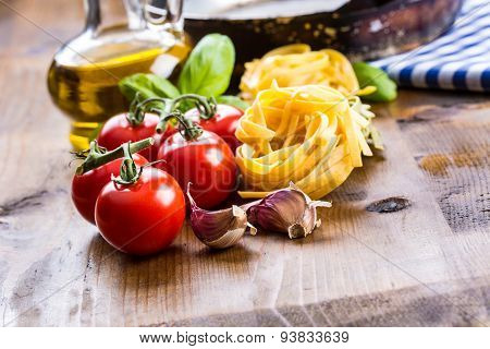 Italian and Mediterranean food ingredients on wooden background.Cherry tomatoes pasta