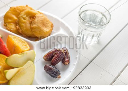 Dates with fruits and fried snacks. Food to break fast during holy month of Ramadan.
