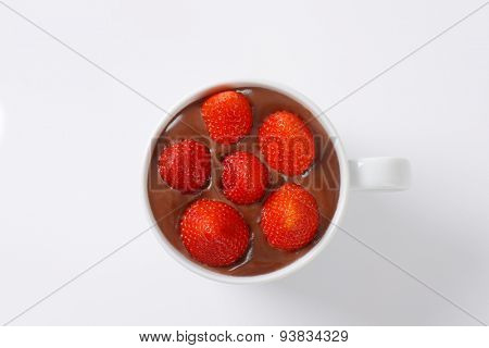 mug of strawberries in chocolate pudding on white background