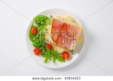slices of fresh bread with dried pork ham, rucola and spinach leaves and halved cherry tomatoes on white plate