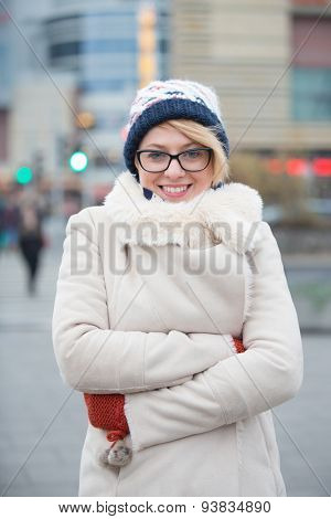 Portrait of happy woman in warm clothing standing arms crossed on city street