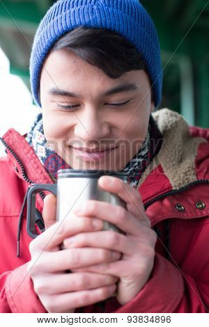 Smiling man looking at coffee in insulated drink container during winter