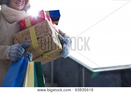 Midsection of woman with stacked gifts and shopping standing by window during winter