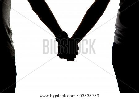 Silhouette of two holding hands