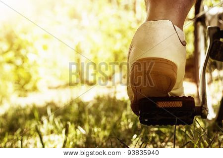 Shoe On The Bike Pedal In Front Of Bloomy Sunny Nature Background