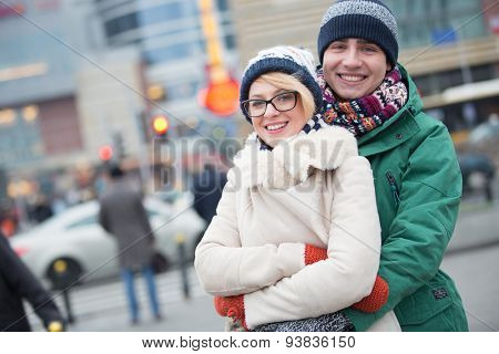 Portrait of happy couple embracing on city street during winter
