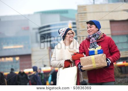 Happy couple with gifts and shopping bags walking in city during winter