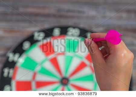 Hand holdin red arrow and throwing to dart board