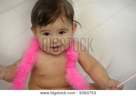 naked baby girl sitting and smiling with pink feathers