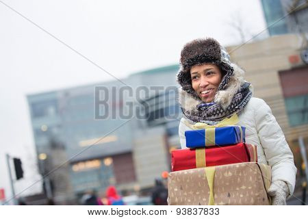 Happy woman looking away while carrying stacked gifts during winter