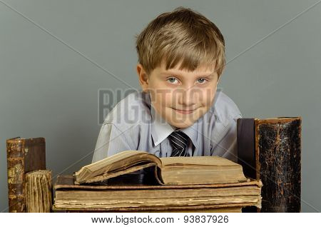 The boy is trying to learn and read old books