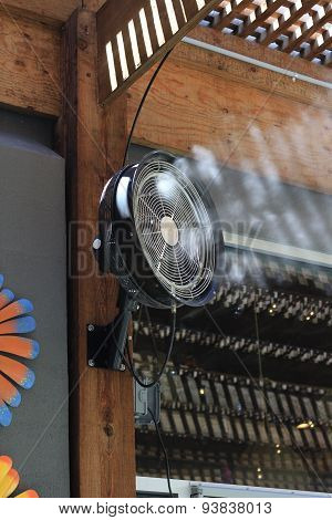 Fan blowing with water mist.