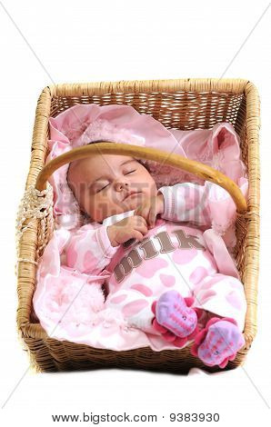 baby girl in pink laying in a brown basket draped with white beads